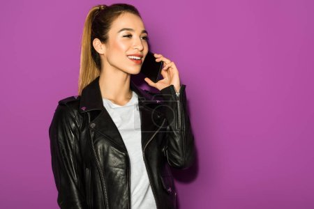 beautiful smiling asian girl talking by smartphone and looking away isolated on violet