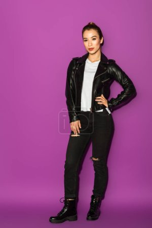 full length view of beautiful stylish asian girl in leather jacket looking at camera isolated on violet