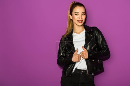 beautiful stylish asian girl in leather jacket smiling at camera isolated on violet