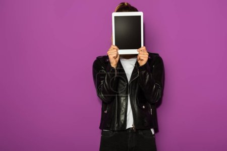 stylish young woman in leather jacket hiding face with digital tablet isolated on violet