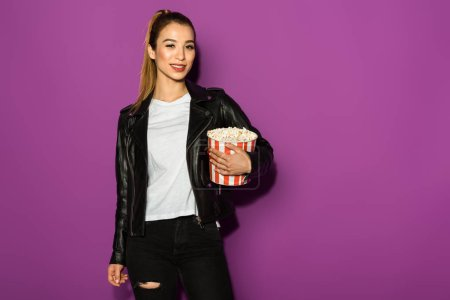 Photo for Beautiful stylish asian girl holding box of popcorn and smiling at camera isolated on violet - Royalty Free Image