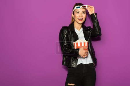 beautiful happy asian girl in 3d glasses holding popcorn and smiling at camera isolated on violet
