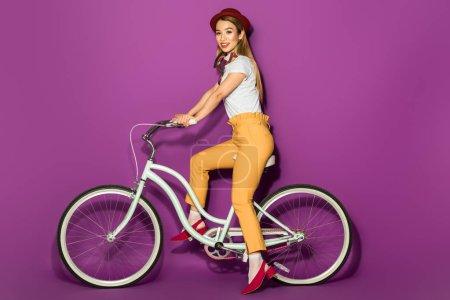 Photo pour Belle élégant asiatique fille équitation vélo et sourire à la caméra isolé sur violet - image libre de droit