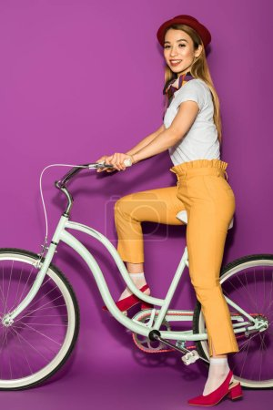 full length view of happy stylish asian girl riding bicycle and smiling at camera isolated on violet