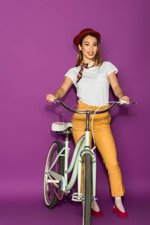 full length view of beautiful stylish asian woman standing with bicycle and smiling at camera isolated on violet