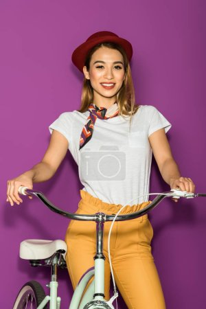 beautiful asian girl standing with bicycle and smiling at camera isolated on violet