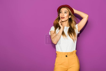 Photo for Beautiful stylish asian girl in hat posing and looking away isolated on violet - Royalty Free Image