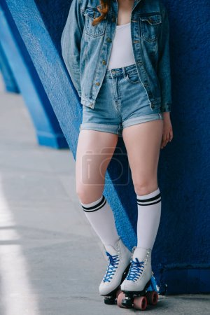 cropped shot of stylish woman in denim clothes, high socks and retro roller skates