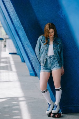 stylish woman in denim clothes, high socks and retro roller skates leaning on blue wall