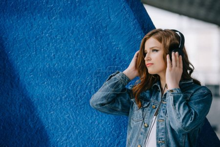 side view of young beautiful woman listening music in headphones
