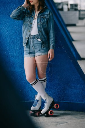 partial view of fashionable woman in denim clothing and retro roller skates listening music in headphones