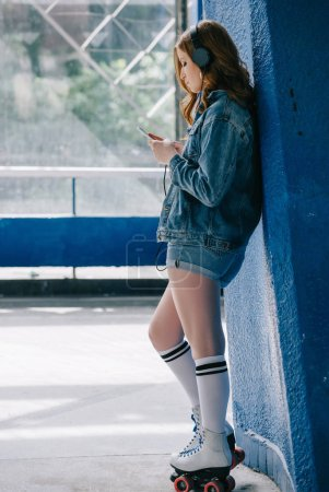 side view of stylish woman in headphones, denim clothing, high socks and roller skates using smartphone