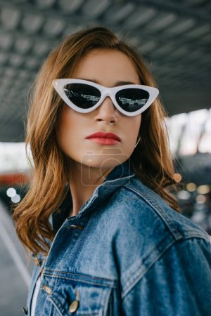 portrait of young fashionable woman in denim clothing and retro sunglasses