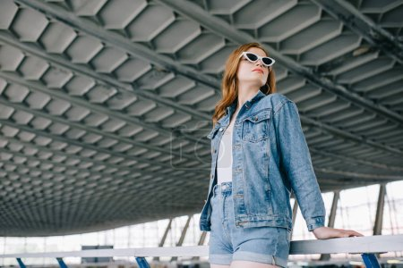 low angle view of young fashionable woman in denim clothing and retro sunglasses