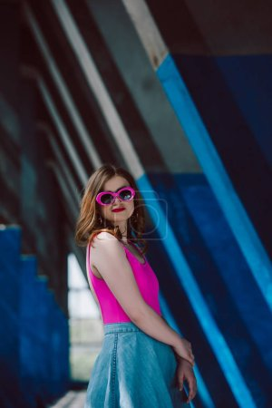 Photo for Portrait of stylish smiling woman in pink retro sunglasses and denim skirt - Royalty Free Image