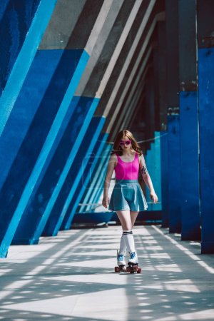 stylish girl in pink sunglasses and denim skirt roller skating and looking down