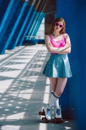 beautiful girl in sunglasses, denim skirt and roller skates standing with crossed arms and looking at camera