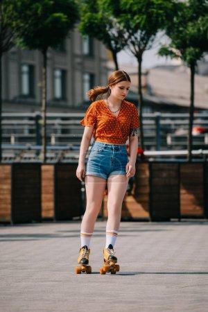 beautiful stylish girl in denim shorts roller skating on street