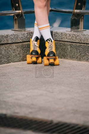 cropped shot of girl in socks and vintage roller skates standing on street