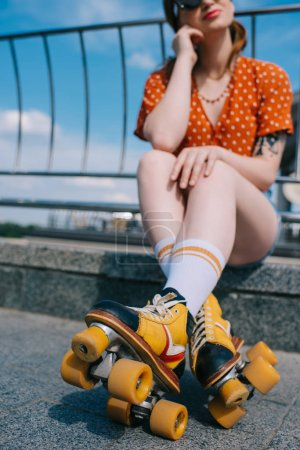 cropped shot of stylish girl in vintage roller skates sitting on street