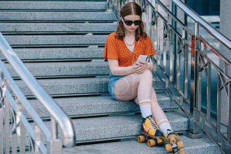 belle fille en lunettes de soleil et patins à roulettes assis sur les escaliers et écouter de la musique avec smartphone