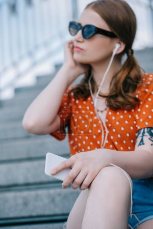 Photo for Selective focus of girl in sunglasses and earphones listening music with smartphone while sitting on stairs - Royalty Free Image