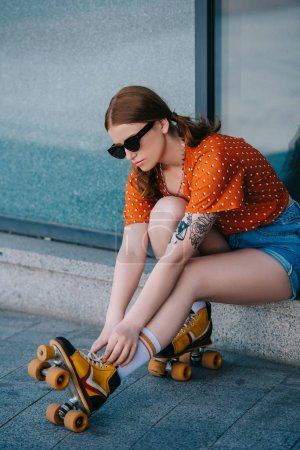 Photo for Stylish girl in sunglasses wearing roller skates while sitting on street - Royalty Free Image