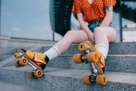 cropped shot of stylish young woman in roller skates sitting on stairs