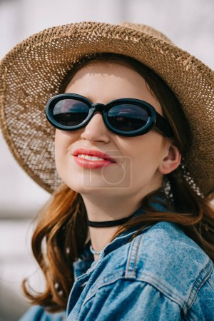 portrait of happy young woman in sunglasses, hat and denim jacket smiling outdoors