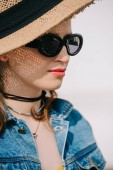 portrait of beautiful young smiling woman in hat and sunglasses looking away