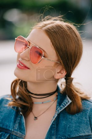 portrait of beautiful smiling girl in sunglasses and denim jacket looking away outdoors