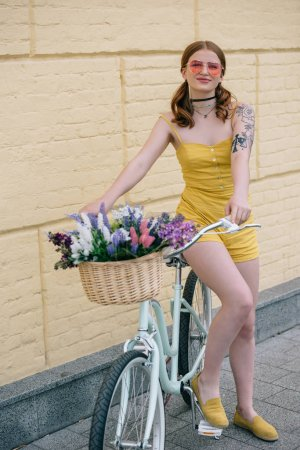 Photo for Stylish girl in sunglasses smiling at camera while sitting on bicycle with flower basket - Royalty Free Image