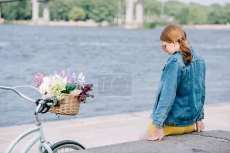 young woman in sunglasses sitting on embankment near bicycle with flower basket