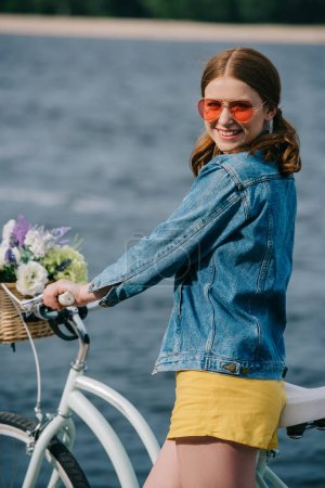 happy attractive girl in sunglasses smiling at camera while standing with bicycle near river