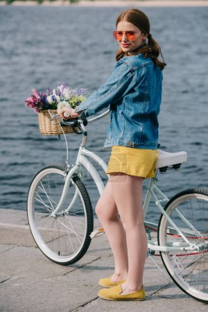 beautiful young woman in sunglasses smiling at camera while standing with bicycle near river