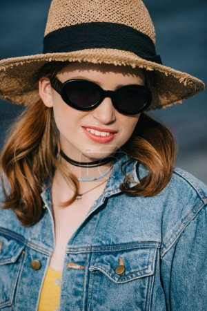 Photo for Portrait of beautiful stylish girl in sunglasses and hat smiling at camera - Royalty Free Image