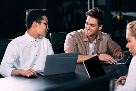multicultural businessmen working and talking at table with laptops at modern office