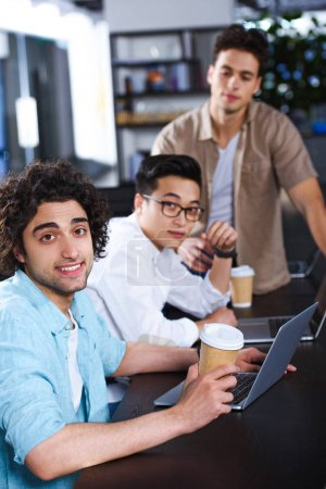 three multiethnic businessmen with paper coffee cups sitting at table with laptops at modern office
