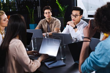 multicultural group of business partners having discussion at table with laptops in modern office