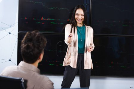 smiling asian businesswoman showing presentation and pointing on male colleague at modern office