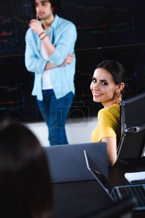young smiling businesswoman looking at camera while her business partner showing presentation at modern office