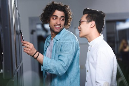 young businessman pointing by pen at board to asian colleague in modern office