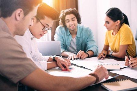 Multikulturelle Gruppe von Geschäftskollegen diskutiert am Tisch mit Diagrammen im modernen Büro