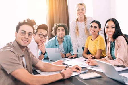 group of smiling multicultural business partners sitting at table with laptops and papers during meeting at modern office