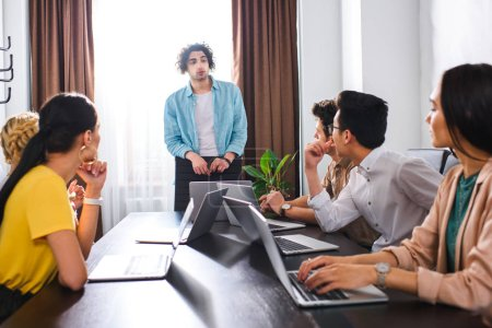 multiethnic businesspeople sitting at table with laptops during meeting at modern office