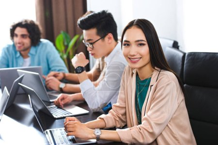 young asian businesswoman looking at camera at table with laptops and businessmen working behind at modern office
