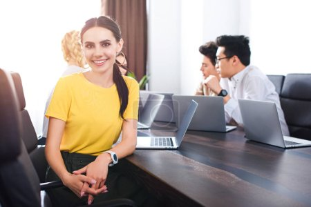 smiling young businesswoman looking at camera while her partners having discussion behind at modern office