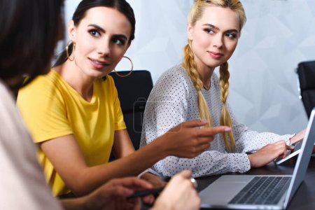 businesswoman pointing by finger at laptop screen to colleague in modern office