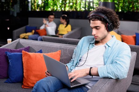 young businessman in headphones sitting on couch with laptop at modern coworking office