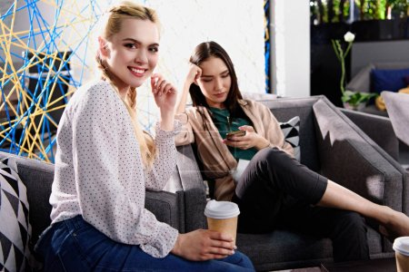smiling businesswoman with paper cup of coffee and asian businesswoman with smartphone behind at modern coworking office